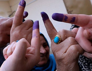 Iraqis voters show their his ink-stained fingers after casting their votes inside a polling station in the country's parliamentary elections in Ramadi, Iraq.