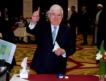 Iraqi President Fuad Masum shows his ink-stained finger after casting his vote in the country's parliamentary elections in the heavily fortified Green Zone in Baghdad, Iraq.
