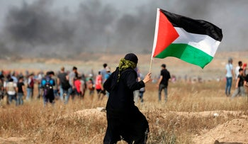 A Palestinian demonstrator carries the national flag during clashes with Israeli forces along the border of the Gaza strip, on May 11, 2018,