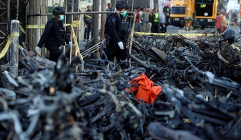 Members of the Indonesian Special Forces Police counter-terrorism squad walk by burned motorcycles following a blast at the Pentecost Church Central Surabaya (GPPS), in Surabaya, Indonesia May 13, 2018.