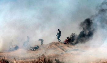 Palestinian demonstrators react to teargas during clashes with Israeli forces along the border with the Gaza strip, east of Gaza City, on May 11, 2018