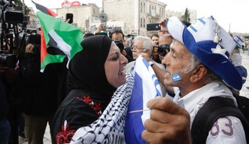 A Jewish man and Palestinian woman confront each other at the beginning of the Flag March on May 13, 2018.