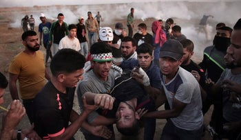 Palestinian protesters carry an injured man during a protest at the Gaza Strip's border with Israel, Friday, May 11, 2018.