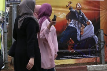 Palestinian women walk past posters marking the 70th anniversary of the Nakba in Ramallah, in the West Bank, on May 13, 2018.