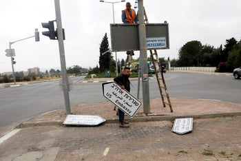 A worker holding a road sign for the U.S. Embassy, near the U.S. Consulate in Jerusalem, May 7, 2018.