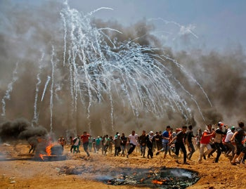 Palestinians run for cover from tear gas during clashes with Israeli security forces near Gaza border,  May 14, 2018