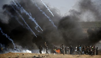 Tear gas is fired at protestors during clashes with Israeli forces near the border between the Gaza strip and Israel, east of Gaza City on May 14, 2018