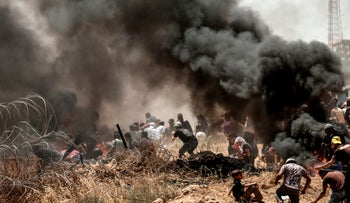 Palestinians clash with Israeli forces along the border fence between the Gaza Strip and Israel near Gaza City on May 14, 2018.
