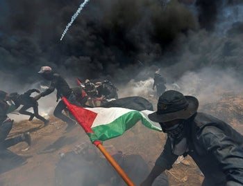 Palestinian demonstrators run for cover from Israeli fire and tear gas near Gaza border, May 14, 2018