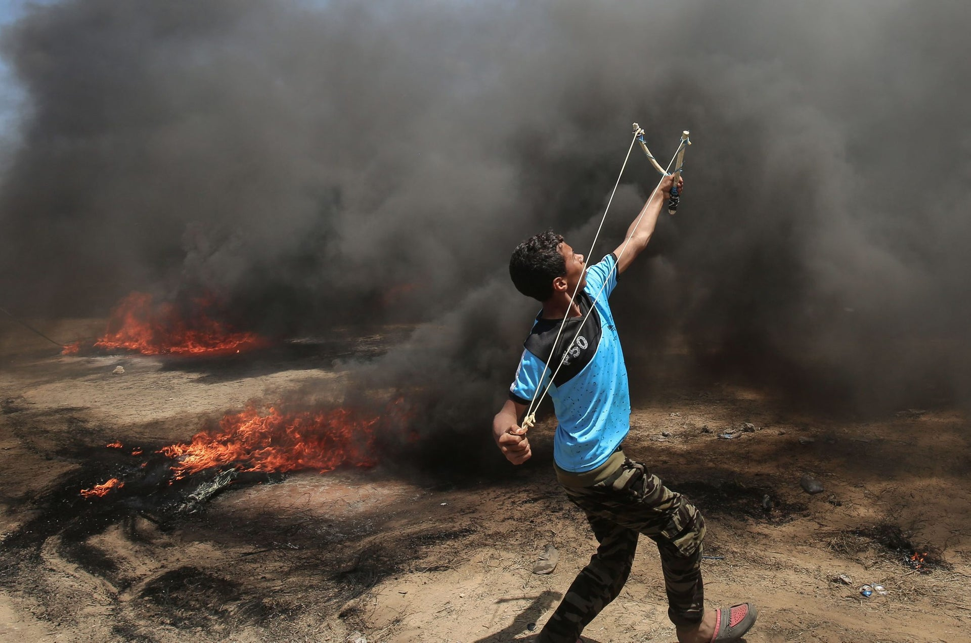 A Palestinian man uses a slingshot during clashes with Israeli forces along the border with the Gaza strip, May 14, 2018