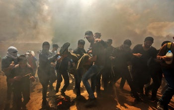 Palestinians carry a demonstrator injured during clashes with Israeli forces near the border between the Gaza strip and Israel east of Gaza City on May 14, 2018.