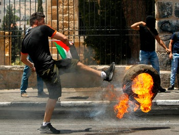 A Palestinian kicks a flaming tire towards Israeli security forces during clashes after a protest marking the 70th anniversary in the West Bank city of Bethlehem on May 15, 2018