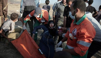 Palestinian medics help a woman who fainted from teargas fired by Israeli troops during a protest at the Gaza Strip's border with Israel, Tuesday, May 15, 2018