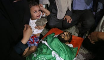 The wife and child of Mohammed Dwedar, a 27 year-old Palestinian killed in clashes along the Gaza border, attend his funeral in Nusseirat refugee camp in the Gaza Strip on May 15, 2018