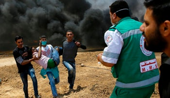 Palestinians carry a wounded protester near the border between Israel and the Gaza Strip, east of Jabalia on May 14, 2018.