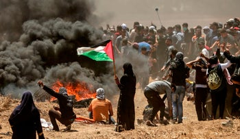 A Palestinian woman holding her national flag looks at clashes with Israeli forces near the border between the Gaza strip and Israel east of Gaza City on May 14, 2018.