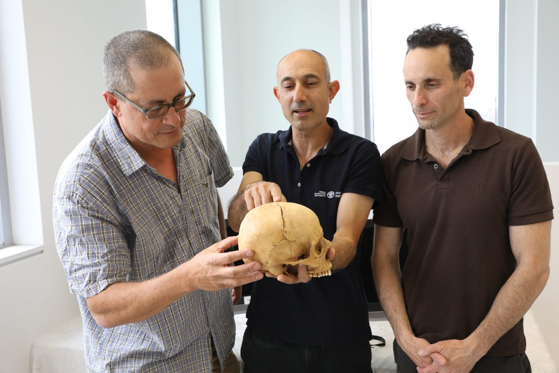 From left: Prof. Boaz Zissu, Dr. Yossi Nagar and Dr. Haim Cohen with the 1,000 year old skull found near Jerusalem that they believe is the earliest known solid evidence of blood vengeance.
