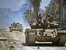 A handout picture released by the official Syrian Arab News Agency (SANA) on May 14, 2018 shows government forces head towards jihadist positions in the Hajar al-Aswad district on the southern outskirts of Damascus
