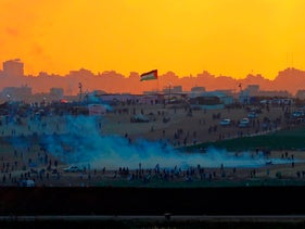 View from the southern Israeli kibbutz of Nahal Oz across the border with the Gaza strip shows tear gas fumes rising amidst Palestinian protesters during clashes along the border. May 15, 2018