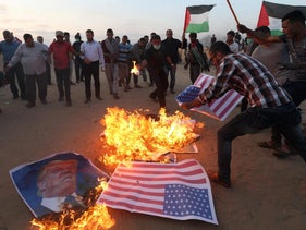 Palestinian demonstrators burn a U.S. flag and a poster of U.S. President Donald Trump at the Israel-Gaza border in the southern Gaza Strip. May 15, 2018.