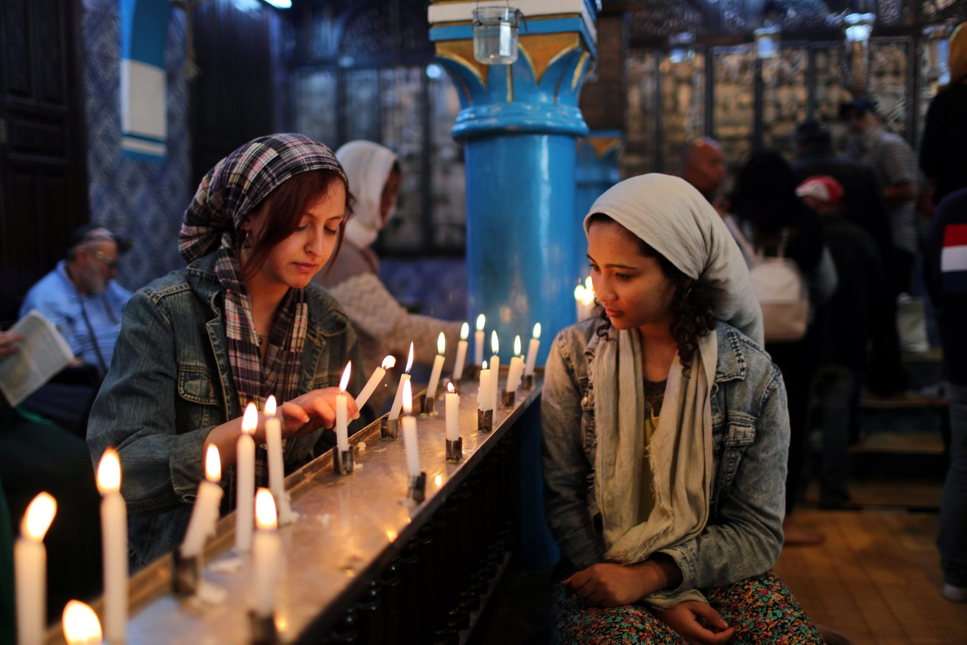 Cyrine Ben Said (L) and Amnia Ben Khalif, Muslim Tunisians, light candles during a religious ceremony at Ghriba, the oldest Jewish synagogue in Africa, during an annual pilgrimage in Djerba, Tunisia May 2, 2018. Picture taken May 2, 2018.