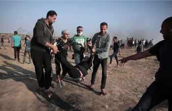 Palestinian protesters carrying a wounded woman during a protest on the Gaza Strip's border with Israel, May 15, 2018.