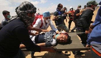 Palestinians carry a protester injured during clashes with Israeli forces along Gaza border, May 14, 2018