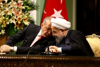 Turkish President Recep Tayyip Erdogan, left, speaks with Iranian President Hassan Rouhani