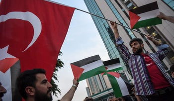 Protesters hold Turkish and Palestinian flags outside Israel's consulate in Istanbul after 60 Palestinians were killed in Gaza, May 16, 2018.