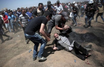 An elderly Palestinian man falls on the ground after being shot by Israeli troops during a deadly protest at the Gaza Strip's border with Israel, east of Khan Younis, Gaza Strip. May 14, 2018