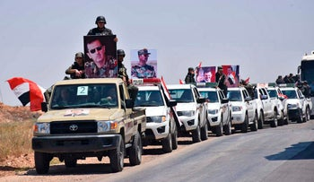 A convoy of Syrian government forces and police hold portraits of Syrian President Bashar Assad, as they enter a village in the northern countryside of Homs province, May 15, 2018.