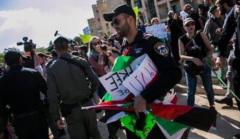 Israeli police hold onto Palestinian flags and placards at a May 13 protest in Jerusalem against the opening of the U.S. embassy there.