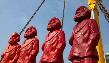 Sculptures of Karl Marx , German philosopher and revolutionary socialist, by German artist Ottmar Hoerl: picture shows four of them, painted a flat red color, being hoisted by chain for transport,  in Trier, southwestern Germany, Thursday April 4, 2013. For an artwork installation.