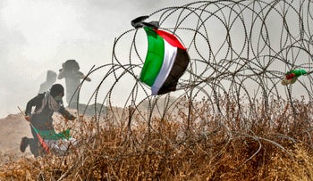 A Palestinian man runs past his national flag during clashes with Israeli forces near the border between the Gaza strip and Israel east of Gaza City on May 14, 2018