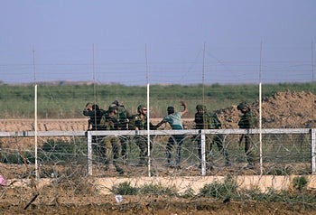Israeli soldiers arrest Palestinian protesters during a protest at the Gaza Strip's border with Israel. May 15, 2018