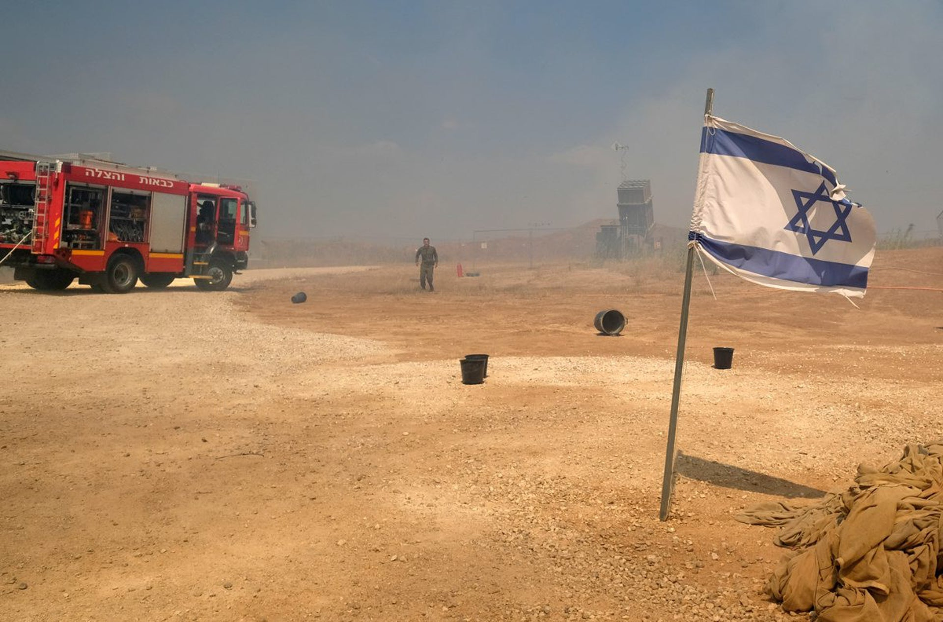 Firefighters and smoke near an Iron Dome battery near the Gaza border.