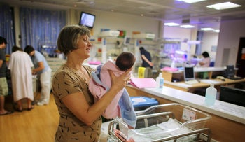 A nurse holds a newborn baby at a nursery in Hadassah Ein Kerem Medical Center in Jerusalem September 10, 2015.