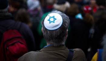 A man wears a Jewish skullcap, as he attends a demonstration against an anti-Semitic attack  in Berlin, Wednesday, April 25, 2018.