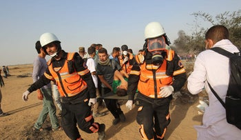 Palestinian health workers evacuate the wounded in demonstrators along the Israel-Gaza border on May 18, 2018.