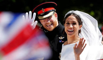 Britain's Prince Harry and his wife Meghan Markle wave as they ride a horse-drawn carriage after their wedding ceremony at St Georgeױs Chapel in Windsor Castle, Windsor, Britain, May 19, 2018.