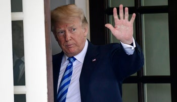 U.S. President Donald Trump waves from the White House, in Washington, May 16, 2018.