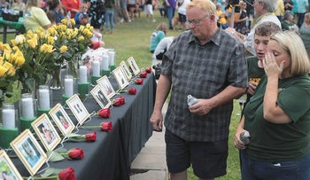 Pictures of victims of the Santa Fe High School shooting are displayed during a prayer vigil at Walter Hall Park on May 20, 2018 in League City, Texas