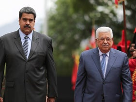 In this handout photo released by the Miraflores Presidential Press Office, President Nicolas Maduro, left, walks with Palestinian President Mahmud Abbas as they review the honor guard during a welcoming ceremony at the Miraflores Presidential Palace in Caracas, Venezuela, Monday, May 7, 2018. (Marcelo Garcia/Miraflores Presidential Press Office via AP)