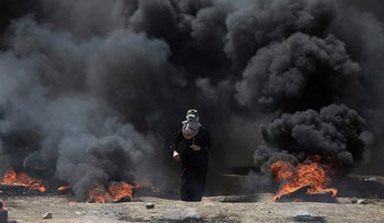 A Palestinian woman walking through black smoke from burning tires during a protest on the Gaza Strip's border with Israel, May 14, 2018.