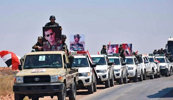 In this photo released Tuesday, May 15, 2018 by the Syrian official news agency, SANA, a convoy of Syrian government forces and police hold portraits of Syrian President Bashar Assad