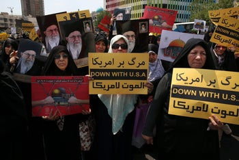 Iranian worshippers hold anti-U.S. and anti-Israel placards at a pro-Palestinian rally after their Friday prayers in Tehran, Iran. May 18, 2018