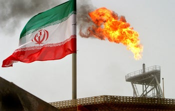 A gas flare on an oil production platform in the Soroush oil fields alongside an Iranian flag in the Persian Gulf, Iran. July 25, 2005