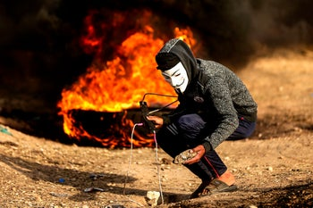 A Palestinian protester wearing a Guy Fawkes mask and holding a slingshot during clashes with Israeli soldiers along the border with the Gaza Strip, May 18, 2018.