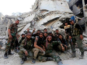 Syrian government forces pose for a photo in front of destroyed buildings at the entrance of the Palestinian camp of Yarmuk on the southern outskirts of Damascus on May 21, 2018.