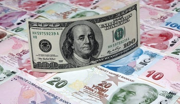 FILE PHOTO: A photo illustration taken in Istanbul shows a U.S. 100 dollar banknote against Turkish lira banknotes of various denominations January 7, 2014.